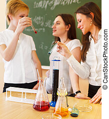 Girls working in chemistry laboratory with liquid formula
