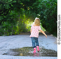 Cute little girl wearing rain boots jumping into a puddle