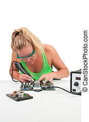 Woman soldering - Beautiful woman repairing a printed...