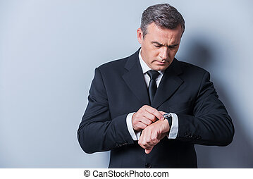 Businessman checking the time Confident mature man in...
