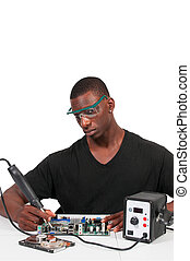 Man soldering - Man repairing a printed circuit board with a...