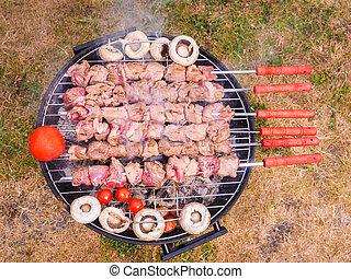 Shish kebab prepared over a black round shaped charcoal...