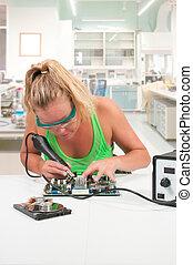 Woman soldering - Beautiful woman repairing a printed...