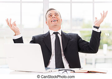 Confident and successful. Happy mature man in formalwear smiling and gesturing while sitting at his working place