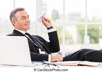Chill time. Playful mature man in formalwear holding paper...