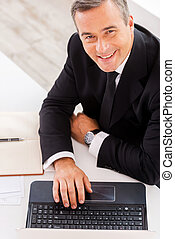Businessman at work. Top view of happy mature man in...