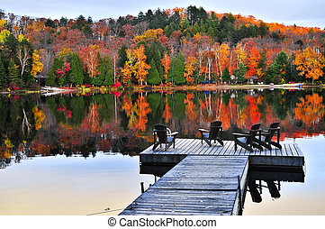 Wooden dock on autumn lake - Wooden dock with chairs on calm...