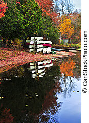 Fall forest reflections with canoes - Canoes at forest of...