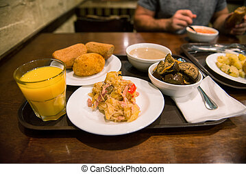People eat ordinary food on a tray on the table in the...