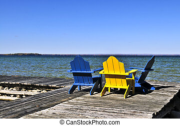 Chairs on wooden dock at lake - Painted wooden chairs on...