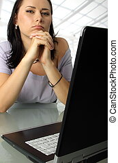Serious woman behind a laptop - Serious female is sitting...