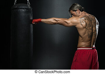 Boxer With Punch Bag In Action - A Man With A Tattoo In Red...