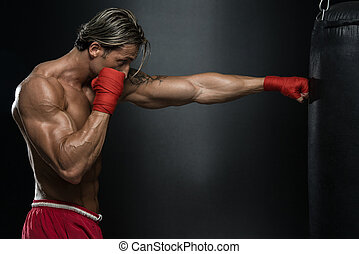 Mature Man Exercising Bag Boxing In Studio - A Man With A...