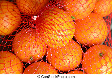 Fresh orange oranges in plastic netting In Market Food...