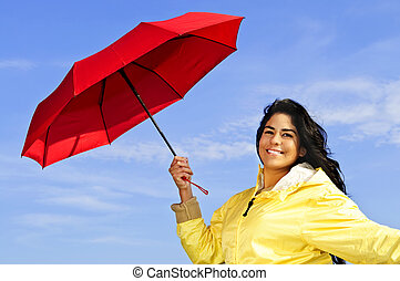 Beautiful young woman in raincoat with umbrella - Portrait...