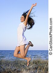 Beautiful brunette jumping in the beach - Beautiful brunette...