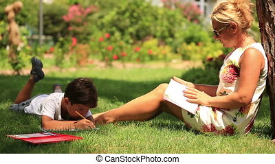 Mother and son relaxing - Child painting, mother reading a...