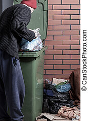 Homeless looking for something in the trash - Homeless man...