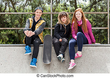 Teenagers sitting on a halfpipe - Young friends sitting on a...