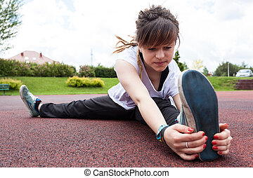 Teenager stretching in a park - Teenage girl with dreadlocks...