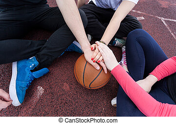 Friends holding hands on basketball - Group of friends...