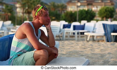 young man sitting - Young man sitting on a beach and...