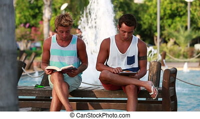 Two young man sitting - Young man sitting at the park and...