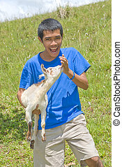 Asian shepherd with young goat - Young Asian laughing...