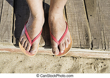 Women foots on the beach Pink thongs Wooden board