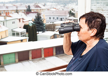 Senior woman with binoculars looking out from window