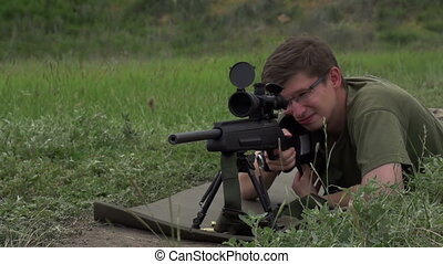 Firing Practice - Sniper in camouflage and sunglasses shoots...