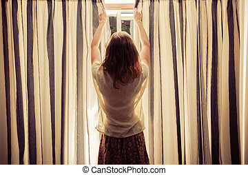 Young woman opening the curtains at sunrise - A young woman...