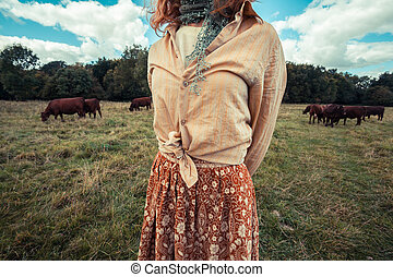 Young woman standing in field with cows
