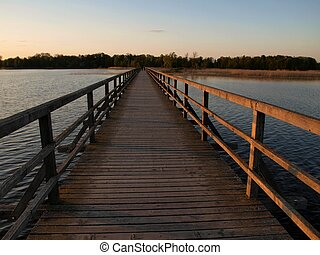 Wooden bridge evening view - Long wooden pier across the...