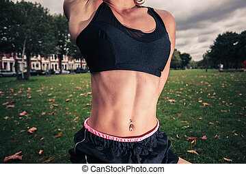 Fit young woman stretching in the park