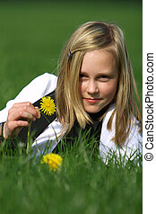 blonde girl smiling and lies in the grass with a flower