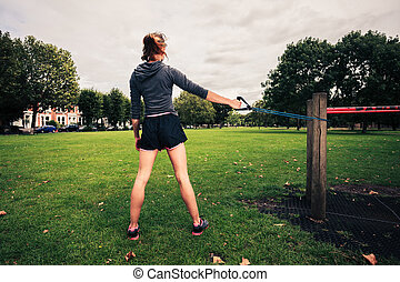 Woman working out with resistance band in the park - A young...