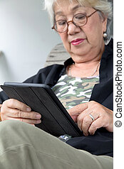 Senior women relaxing at home reading E-book on her tablet.