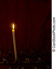 Prayer. Single church candle burns in front of red curtain....