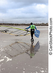 windsurfer finishing up after race and surf on the beach in...