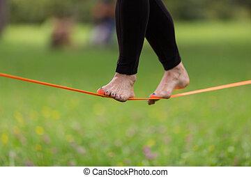 Slack line in the city park - Lady practising slack line in...