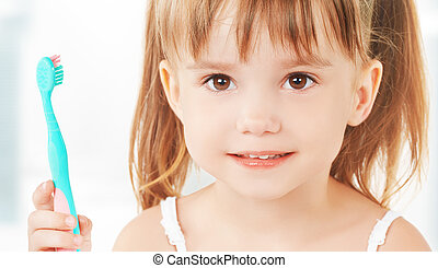 happy little girl brushing her teeth - dental hygiene happy...