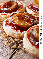 Cakes of puff pastry with plums macro vertical - Cakes of...
