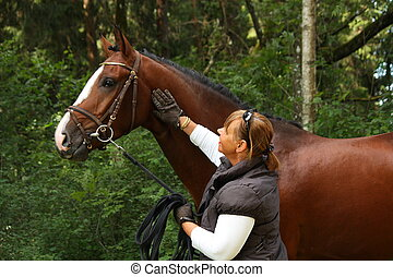 Elderly woman and brown horse portrait in the forest - Happy...