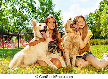 Happy pet owners - Two beautiful teenage girls sitting on...