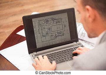 Close-up portrait of laptop with blueprints, architect...