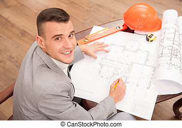 Young handsome architect engineer working on design plan -...