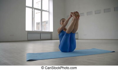 Seated Forward Bend - Woman performing seated forward bend...