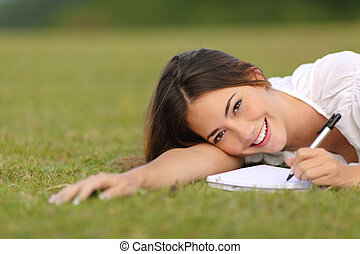Happy woman lying on the grass and writing in a notebook...
