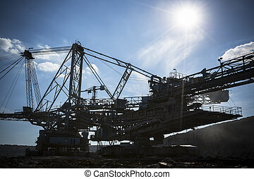 a huge mining machine - a huge working dredge in a mine,...